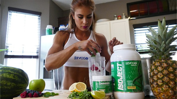 Fitness model located into a kitchen putting  fruit into a blender to create a protein smoothie.