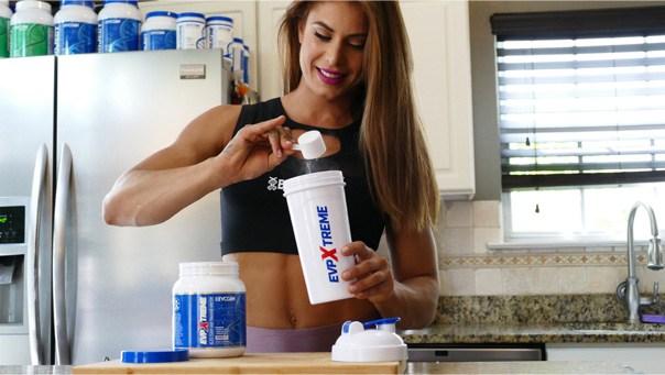 A female exercise model scooping evogen into a protein shake bottle.