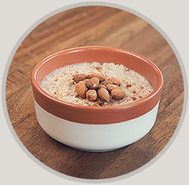 A bowl with oatmeal in and along with some almonds on top.