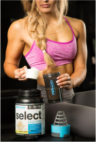 PEScience Athlete putting Select Protein in shaker cup.